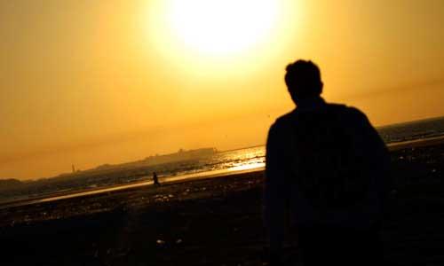 夕焼けの海で遠くを眺める男